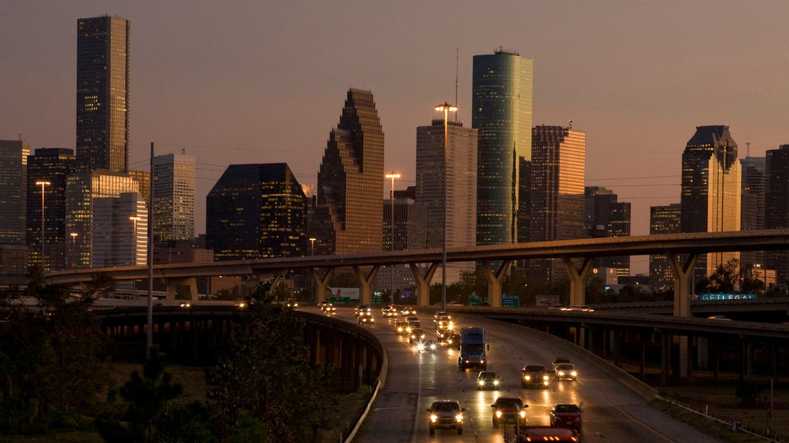 Traffic flows at dusk with the downtown Houston skyline in the background as night falls on America's fastest growing large city October 3, 2008. Even after Hurricane Ike smashed thousands of windows in Houston's skyscrapers last month, times could not be much better in the Petro Metro. While the ill wind of economic turmoil sweeps across America, Houston has been shielded by a combination of low housing prices, a sagging U.S. dollar and surging profits for energy companies based here. Picture taken October 3. To match feature USA-HOUSTON REUTERS/Richard Carson (UNITED STATES)