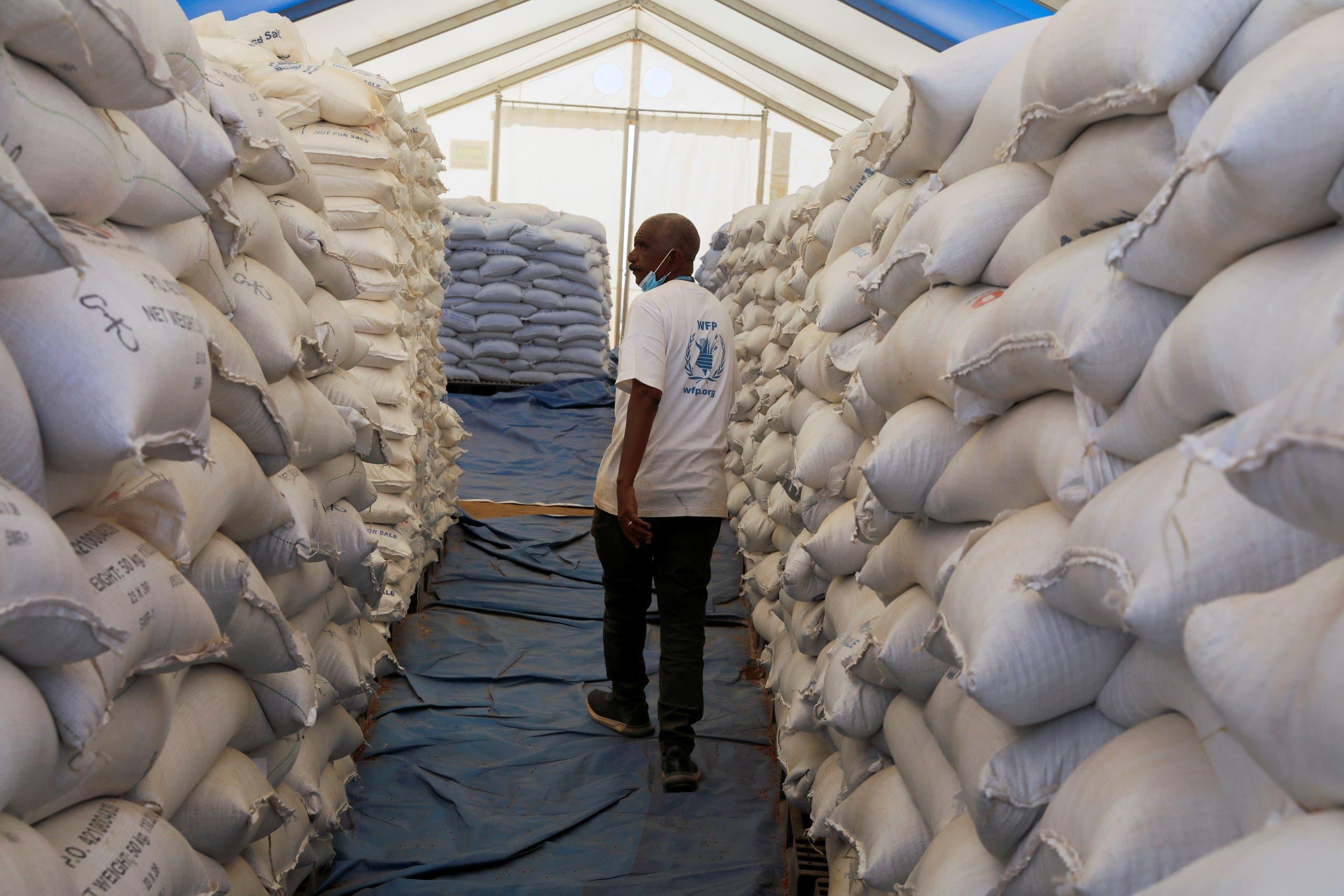 World Food Programme employee walks between sacks of food at the Um Rakuba refugee camp which houses Ethiopian refugees fleeing the fighting in the Tigray region, on the Sudan-Ethiopia border in Sudan, November 29, 2020. (Reuters/Baz Ratner)