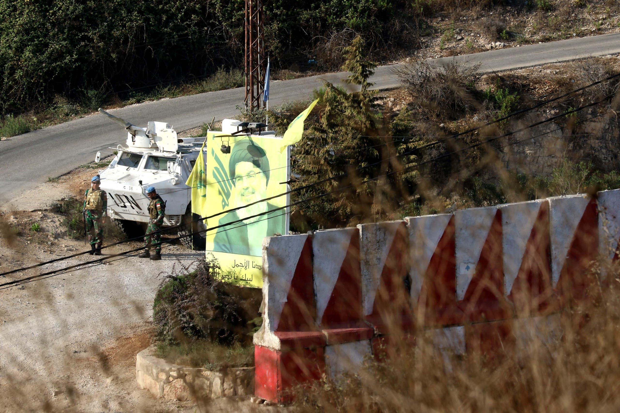آلية لليونيفيل قرب صورة لنصرالله وأعلام لحزب الله في جنوب لبنان (أرشيفية)