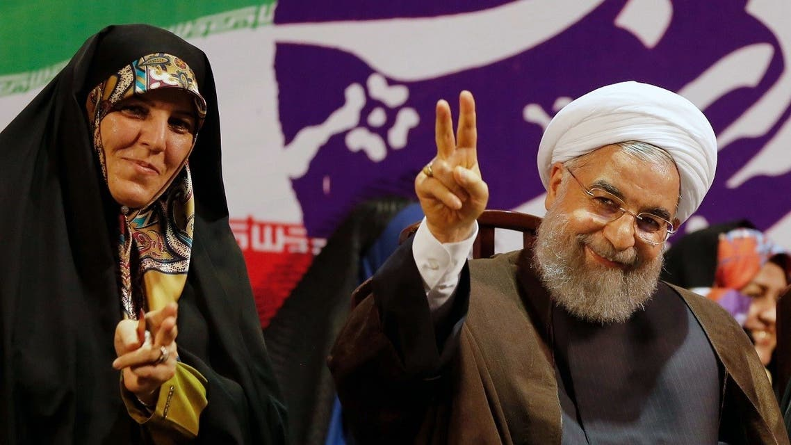Iranian President and presidential candidate Hassan Rouhani gestures during a campaign rally in Tehran on May 9, 2017, with vice president for women's affairs Shahindokht Molaverdi (L) seated next to him. (STR/AFP)