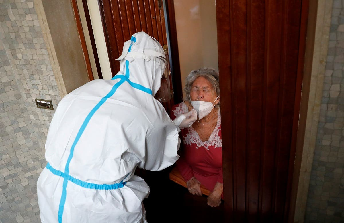 A medical worker visit the home of a patient suspected to be suffering from the coronavirus disease to carry out a swab test, Rome, Italy, December 3, 2020. (Reuters/Remo Casilli)