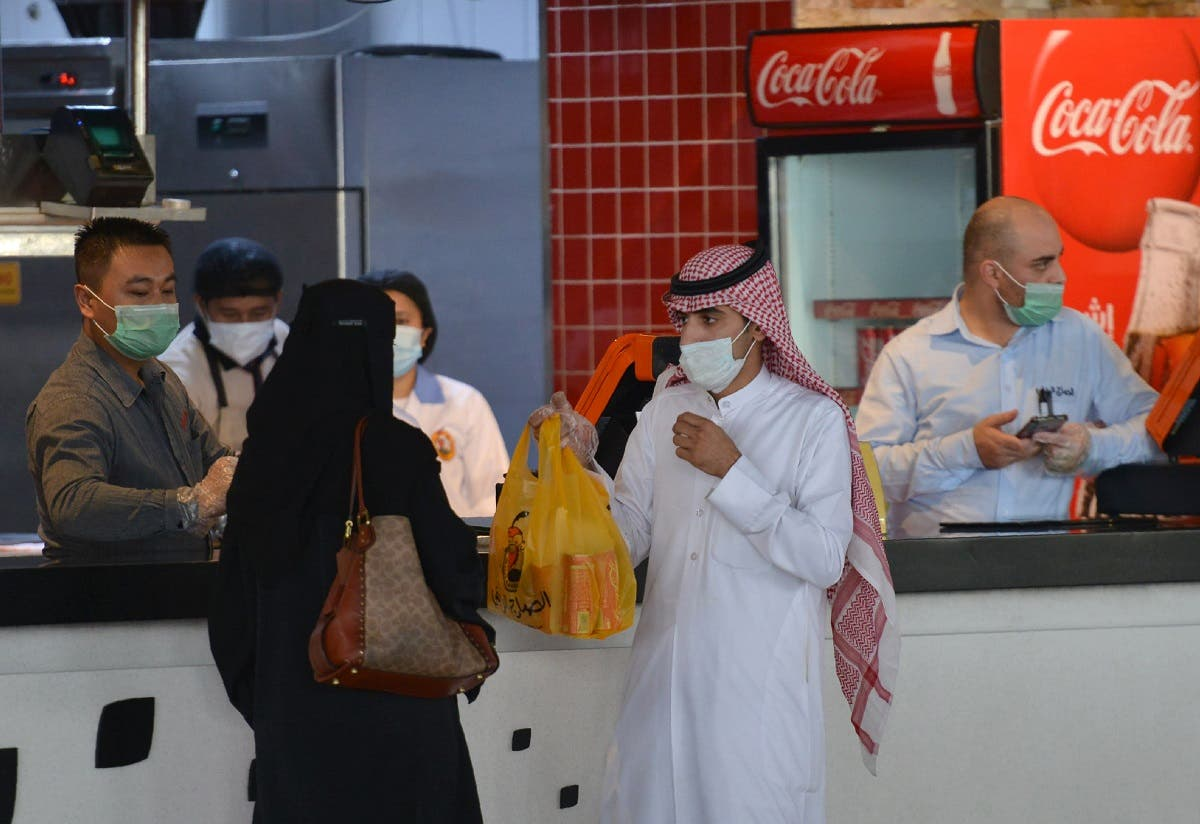 A couple collects an order from a restaurant in a shopping mall in the Saudi capital Riyadh. (File photo: AFP)