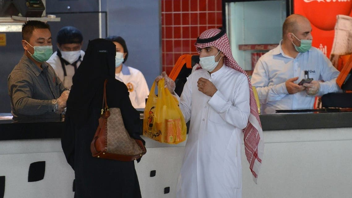 A couple collects an order from a restaurant in a shopping mall in the Saudi capital Riyadh on June 4, 2020, after it reopened following the easing of restrictions to stem the spread of the coronavirus. (Fayez Nureldine/AFP)