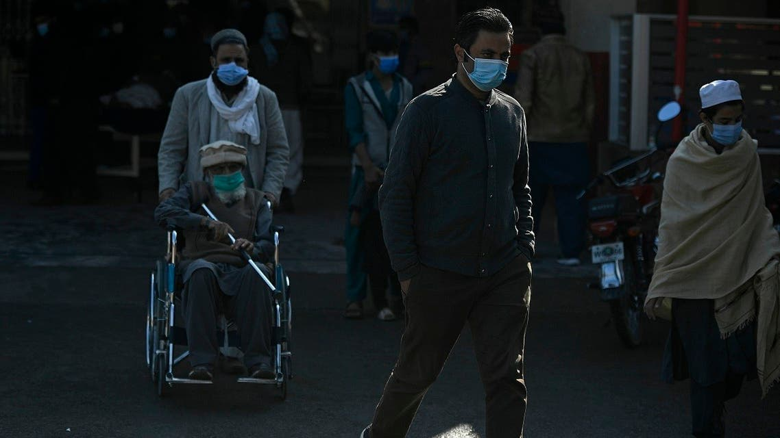 People wearing facemasks as a preventive measure against coronavirus leave from a hospital in Islamabad on November 26, 2020. (Aamir Qureshi/AFP)