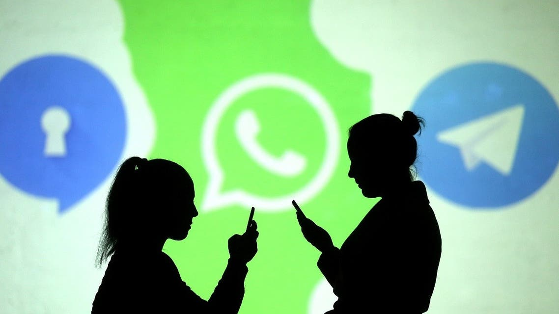 Silhouettes of mobile users are seen next to logos of social media apps Signal, Whatsapp and Telegram projected on a screen in this picture illustration. (Reuters)