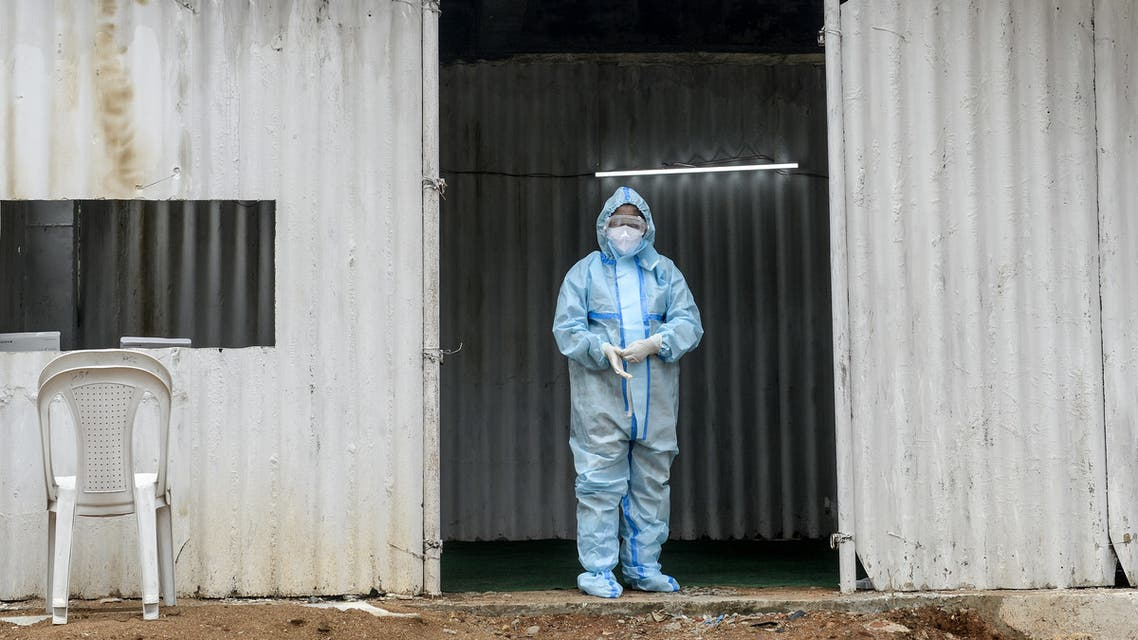 A health worker wearing personal protective equipment (PPE) waits to collect swab samples from residents for Covid-19 coronavirus tests at a temporarory collection centre in Secunderabad, the twin city of Hyderabad on October 1, 2020. (AFP)