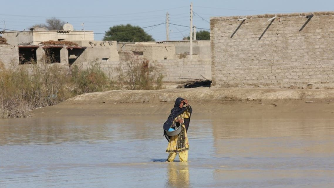 An Iranian woman walks through a flooded road on January 13, 2020 in the village of Dashtiari in Iran's Sistan-Baluchistan region, as severe downpour led to floods across region, blocking roads and damaging homes. (Alireza Masoumi/ISNA/AFP)