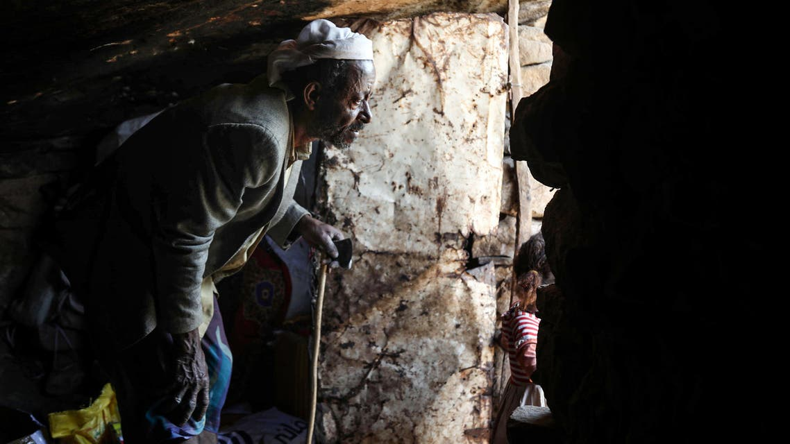 A man at the entrance of a cave where a Yemeni family has sought refuge due to poverty and lack of housing, west of the suburbs of Yemen's third-city of Taez on December 2, 2020. (AFP)