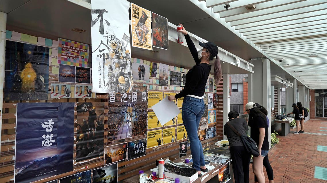 University students put up pro-democracy posters at a Lennon wall in the University of Hong Kong, Tuesday, Sept. 29, 2020. (AP)