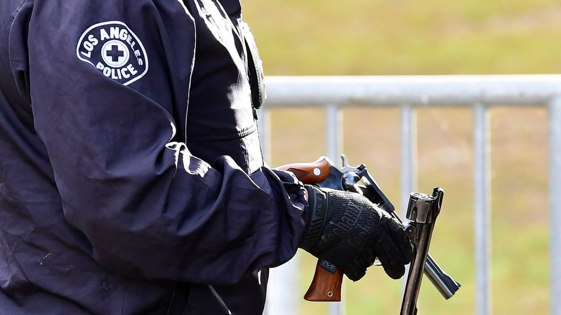 A Los Angeles Police Department officer holds recovered guns. (File photo: AFP)