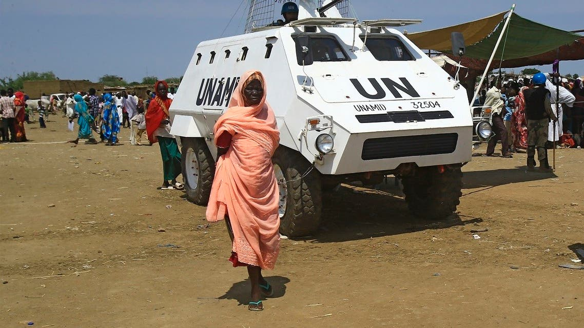 A displaced Sudanese woman walks past a UN-African Union mission to Darfur (UNAMID) vehicle at the Kalma camp for internally displaced people in Darfur's state capital Niyala on October 9, 2019. (AFP)