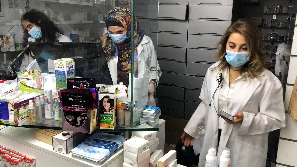 Pharmacist Siham Itani wearing a protective mask looks at her mobile phone inside her pharmacy in Beirut, Lebanon October 6, 2020. (Reuters/Issam Abdallah)