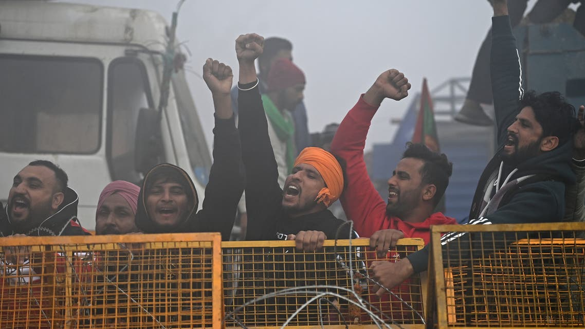 Farmers shout slogans next to a police barricade amid foggy condition during a nationwide general strike to protest against the recent agricultural reforms at the Delhi-Haryana state border in Singhu on December 8, 2020. (AFP)