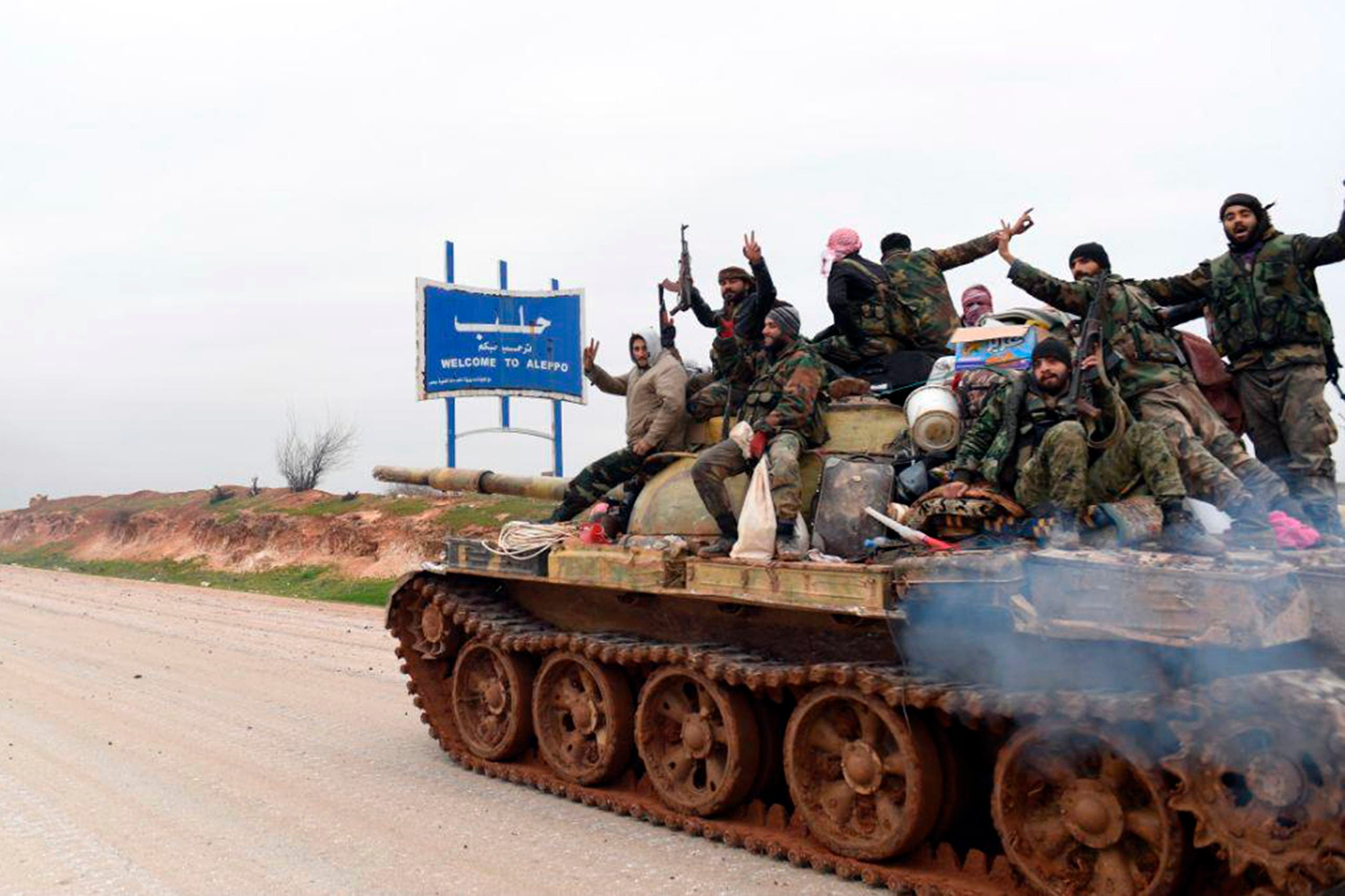 In this photo released Wednesday, February 12, 2020, by the Syrian official news agency SANA, Syrian government soldiers on a tank hold up their rifles and flash victory signs, as they patrol the highway that links the capital Damascus with the northern city of Aleppo. (SANA via The Associated Press)