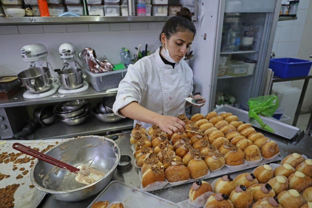 A staff member decorates date-flavoured Abu Dhabi doughnuts created for the Jewish holiday of Hanukkah and in honour to the new diplomatic relations between Israel and the United Arab Emirates, at Kadosh pastry shop in Jerusalem on December 7, 2020. (AFP)
