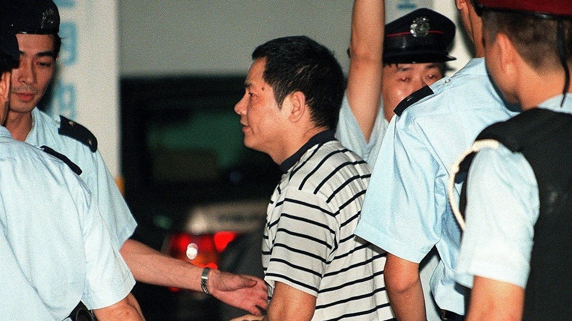 """This file photo taken on May 12, 1998 shows Wan Kuok-koi (C), popularly known by his nickname """"Broken Tooth,"""" being led handcuffed into a Macau courthouse by police for charges of involvement in triad activities. (AFP)"""
