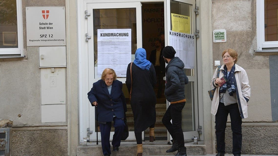 A woman wearing a headscarf leaves a polling station as two elderly women leave the building during general elections in Vienna, Austria, on October 15, 2017. (AFP)