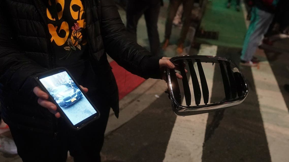A person holds up parts of a car and shows pictures of it at the location of a car that struck multiple pedestrians during a protest on Third Avenue in the Manhattan. (Reuters)
