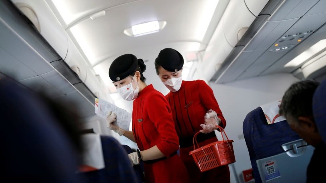 Flight attendants wear protective face masks amid the coronavirus outbreak. (Reuters)