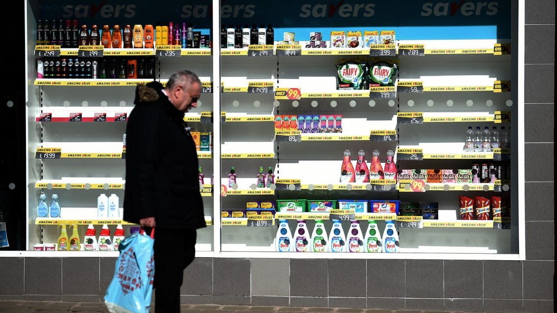 A man carries shopping as he walks past a shop with half-empty shelves in Oldham, Lancashire on March 26, 2020. (AFP)