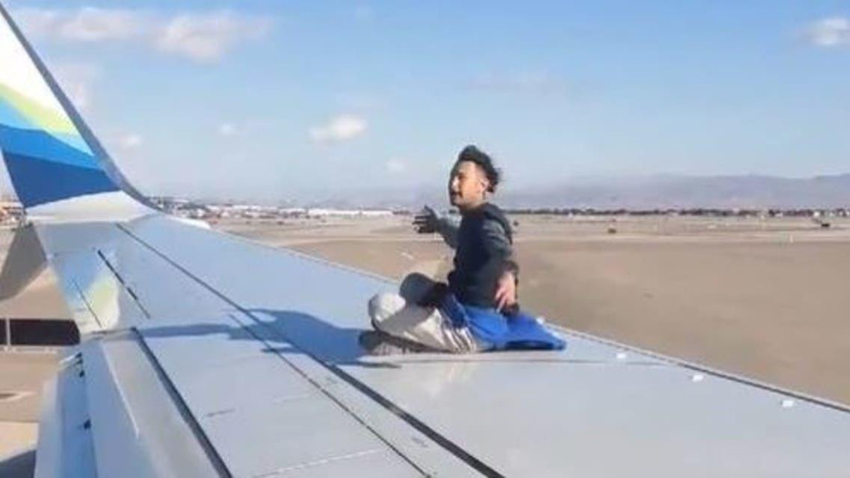 A man spotted on wing of Plane walking