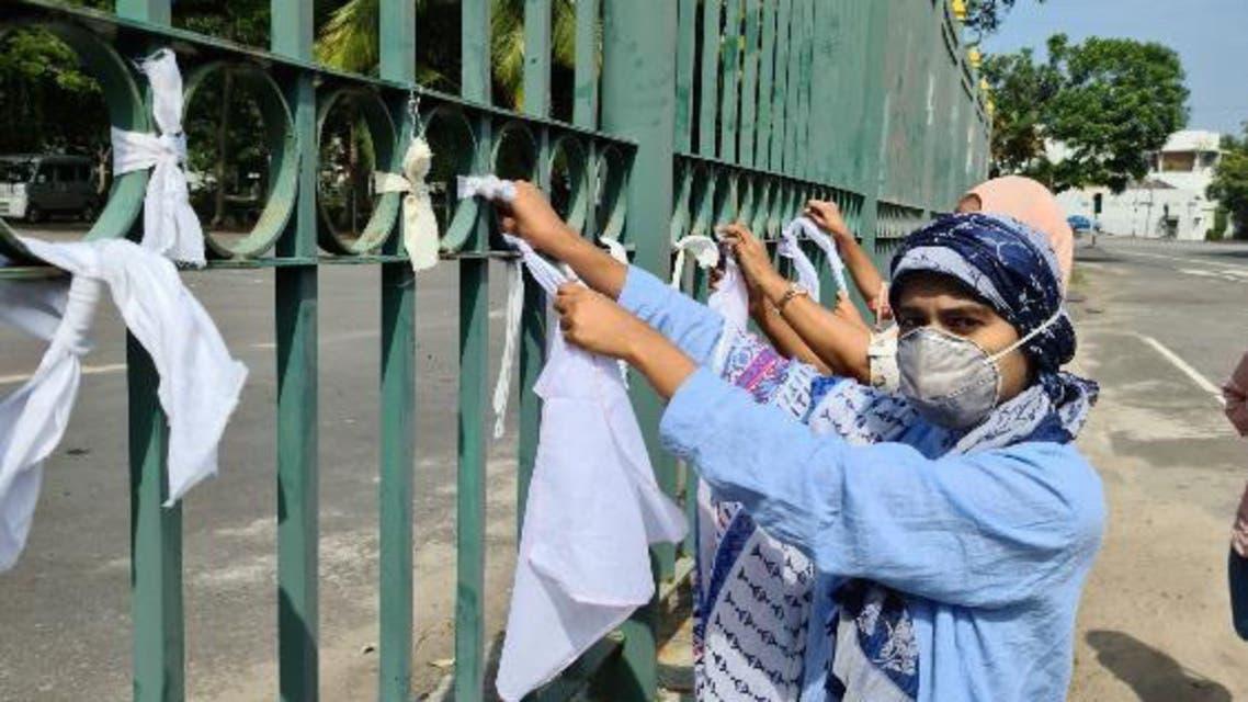Women tie white clothes outside the crematorium in Colombo, Sri Lanka. (Supplied: Razni Razick)