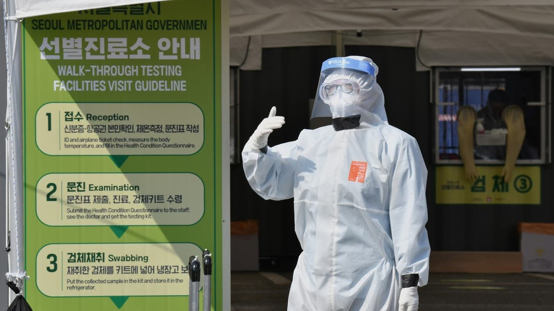 A Seoul city official wearing protective clothing waits to guide visitors for the COVID-19 coronavirus test at a walk-thru testing station set up at Jamsil Sports Complex in Seoul on April 3, 2020. (AFP)