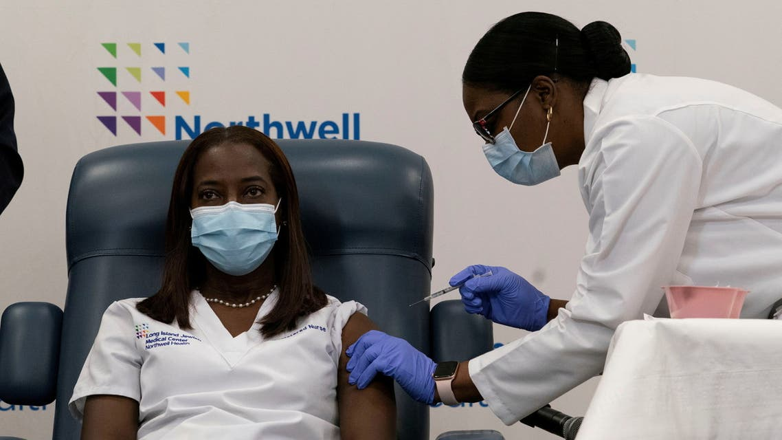 Sandra Lindsay, a nurse at Long Island Jewish Medical Center, is inoculated with the coronavirus disease (COVID-19) vaccine by Dr. Michelle Chester from Northwell Health at Long Island Jewish Medical Center in New Hyde Park, New York, US, December 14, 2020. (Mark Lennihan)