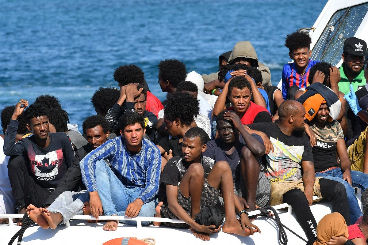 Migrants from Tunisia and Lybia arrive onboard of an Italian Guardia Costiera (Coast Guard) boat in the Italian Pelagie Island of Lampedusa on August 1, 2020. (AFP)
