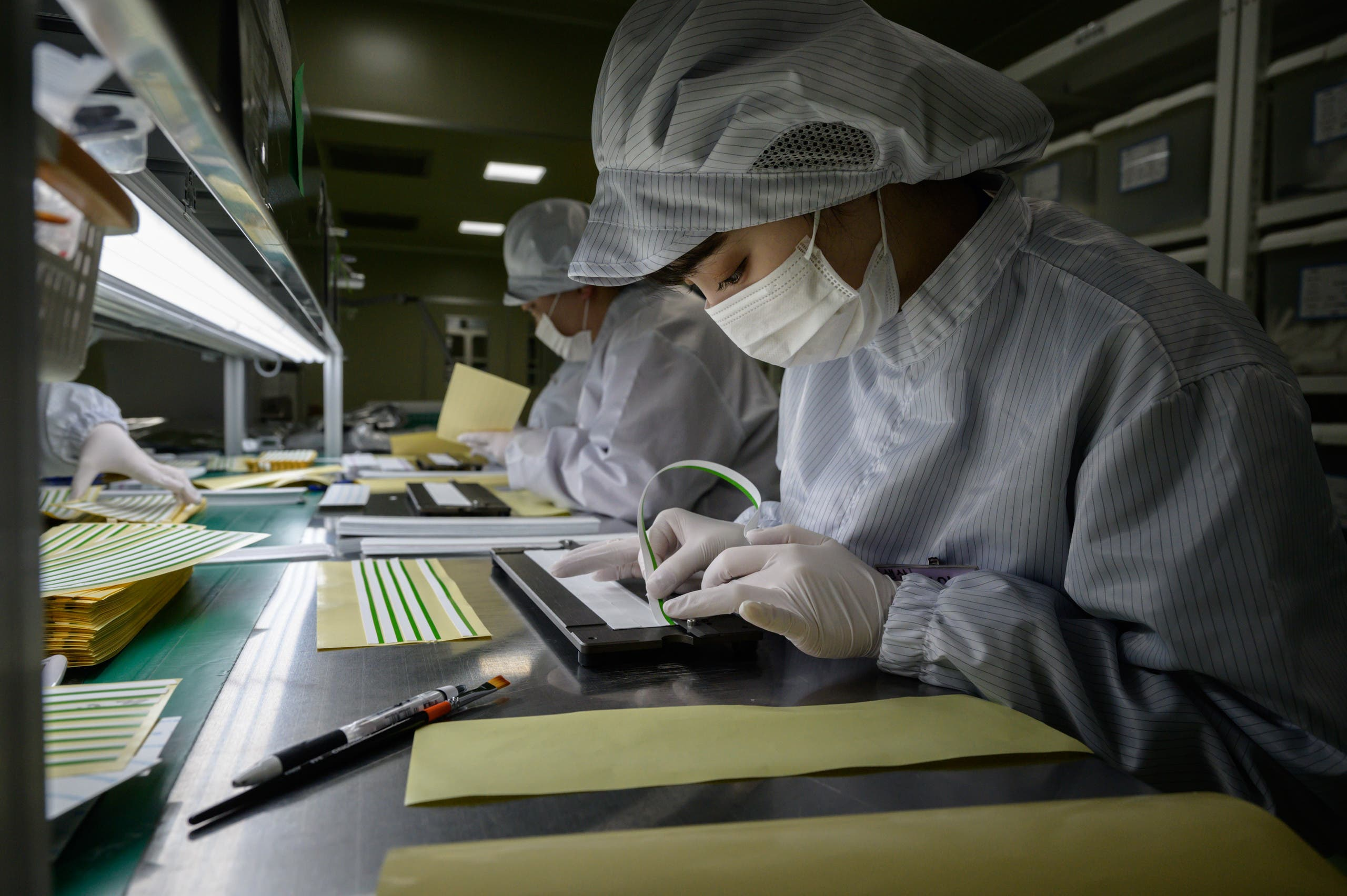 Staff members prepare diagnostic components to be used in COVID-19 novel coronavirus testing kits on a production line at the SD Biosensor bio-diagnostic company near Cheongju, south of Seoul on March 27, 2020. (AFP)