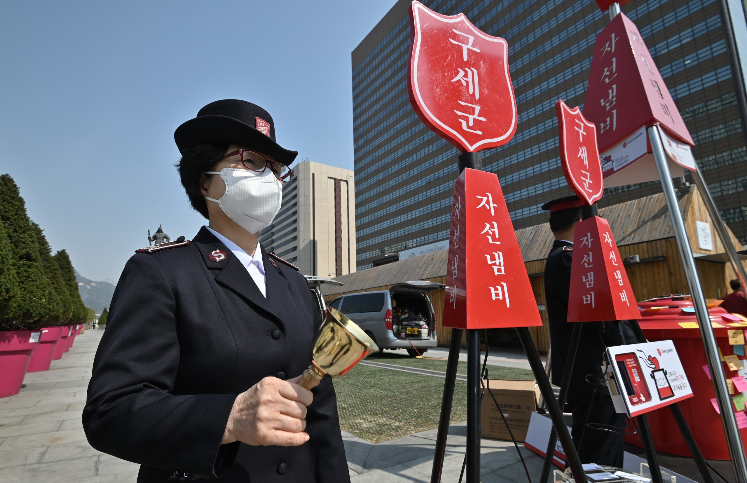 A member of the Salvation Army rings a bell next to a charity pot during a campaign for the donation of face masks in downtown Seoul on March 25, 2020. (AFP)