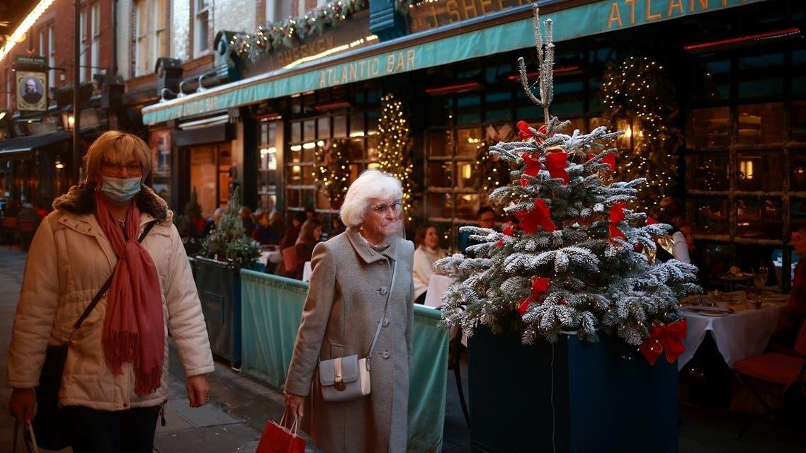 Women walk outside a restaurant following the coronavirus disease (COVID-19) outbreak in London, Britain, on December 15, 2020. (Reuters)