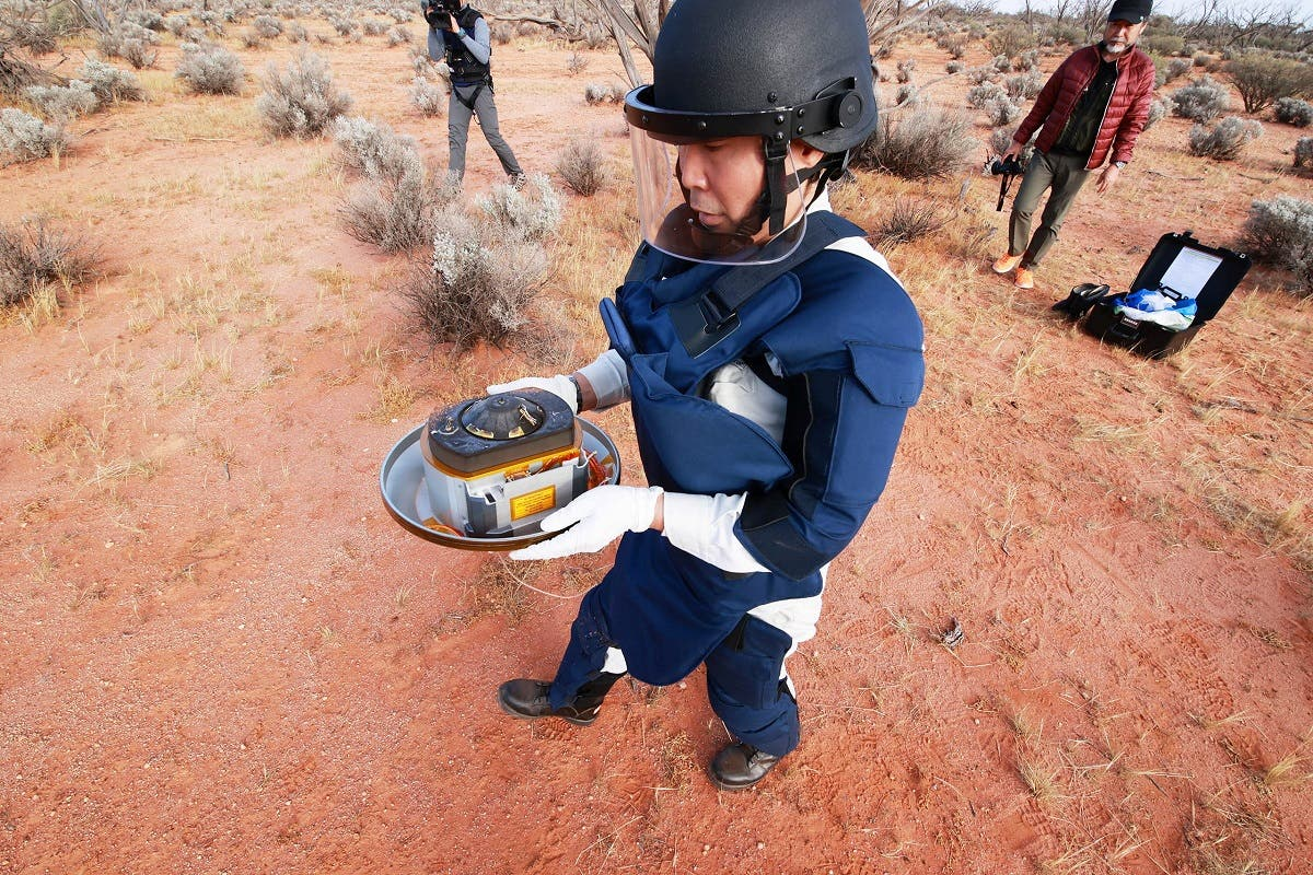A member of Japan Aerospace Exploration Agency (JAXA) collects Hayabusa2's capsule carrying the first extensive samples of an asteroid after it landed in the Woomera restricted area, Australia, on December 6, 2020. (Reuters)