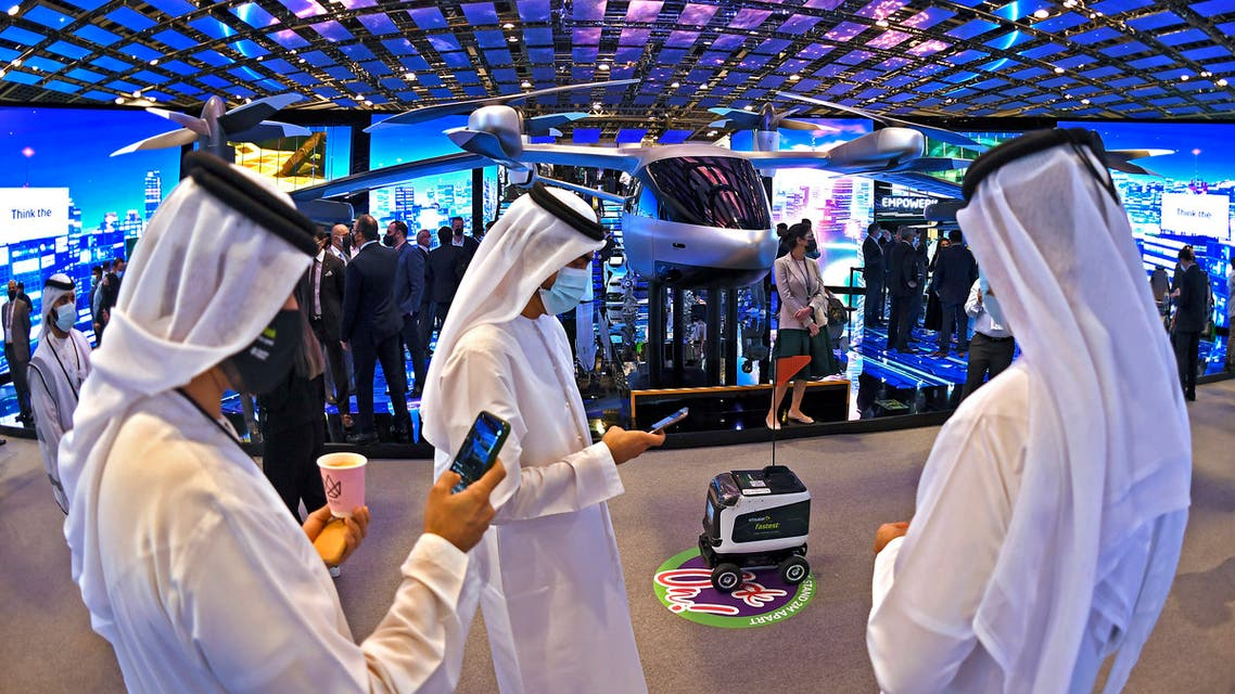 Visitors chat next to a robot at the GITEX 2020 technology summit at the Dubai World Trade center on December 8, 2020. (AFP)