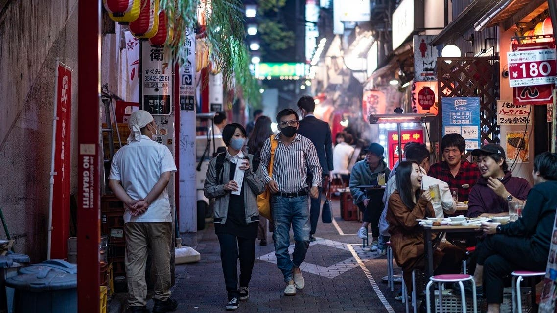 People wearing face masks as a preventive measure against the Covid-19 coronavirus visit the restaurant area of Omoide Yokocho alleyway in Shinjuku district of Tokyo. (AFP)
