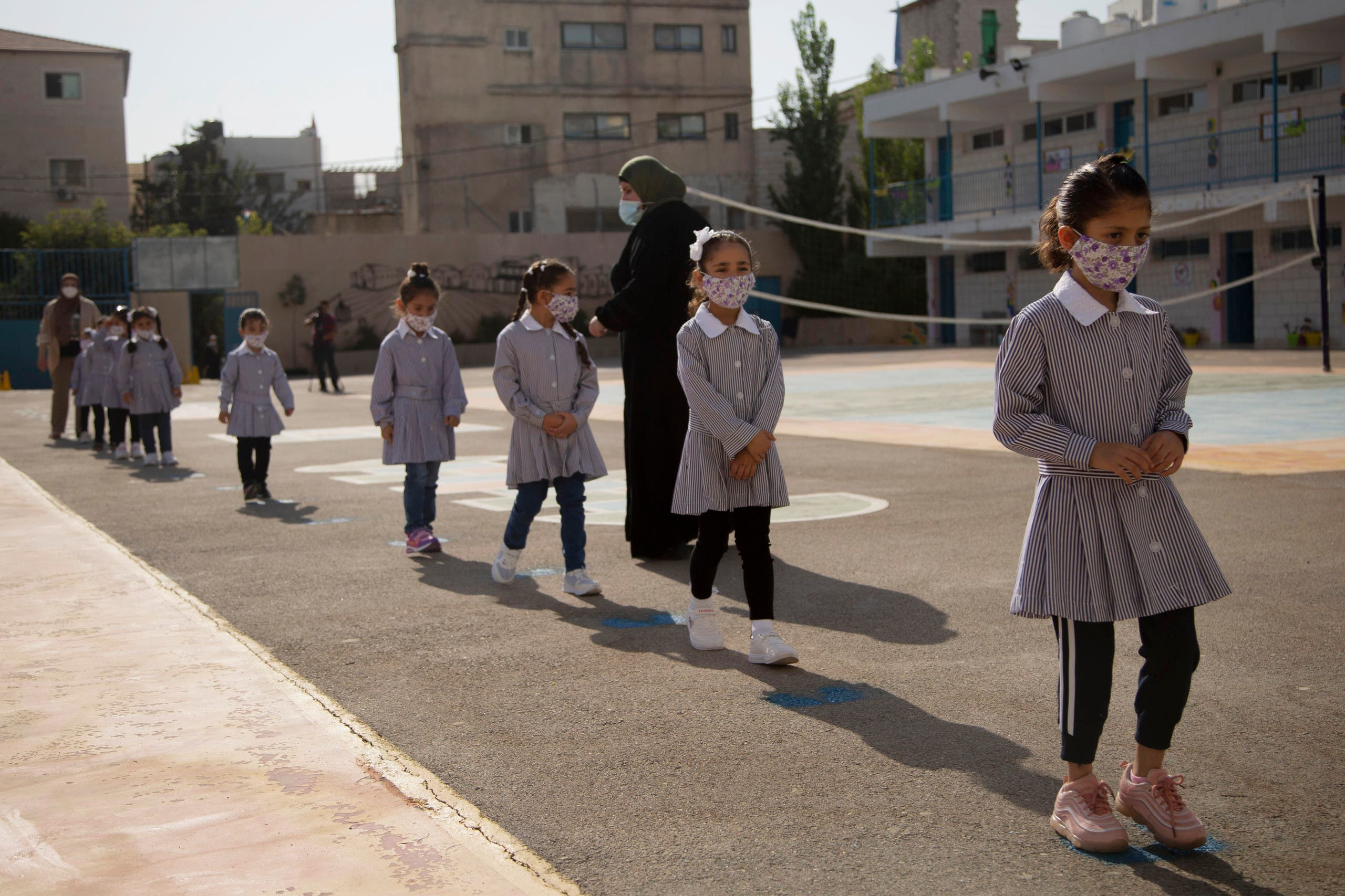 Palestinian elementary school students wearing protective face masks, amid the coronavirus pandemic, enter school on the first day of class at United Nations-run school in the West Bank city of Ramallah, Sunday, September 6, 2020. (The Associated Press/Majdi Mohammed)
