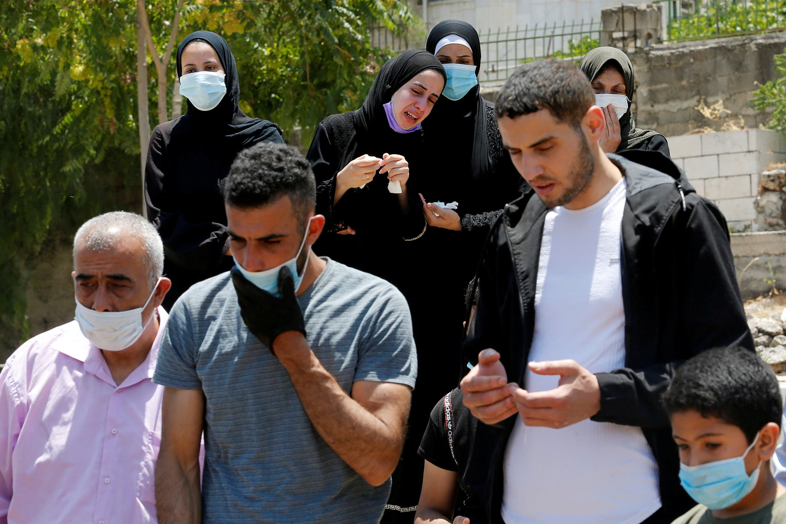 A relative mourns as others attend the burial of a Palestinian man who has died after contracting the coronavirus disease (COVID-19), in a cemetery in Hebron in the Israeli-occupied West Bank July 5, 2020. (Reuters/Mussa Qawasma)