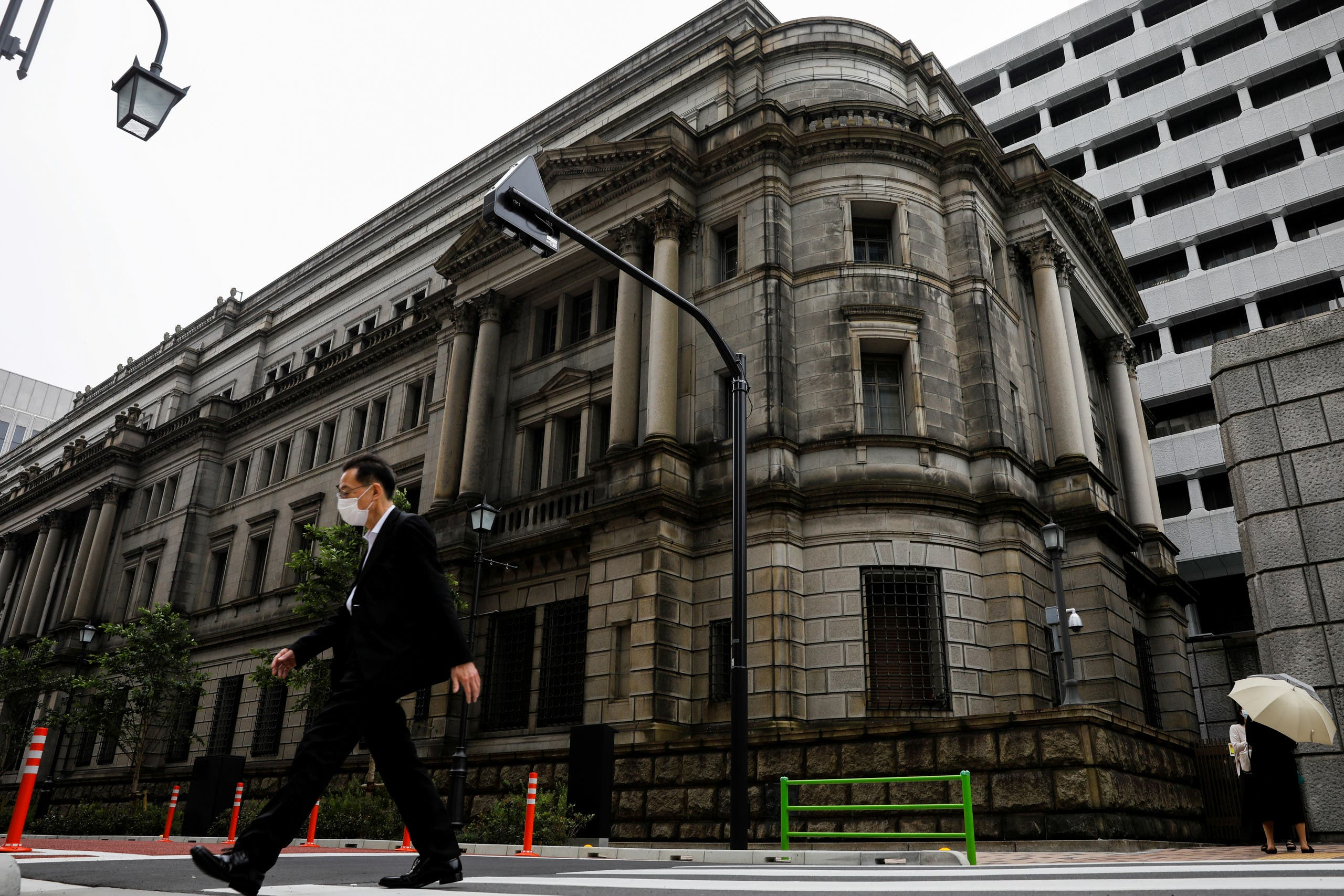 A man wearing a protective mask walks past the headquarters of the Bank of Japan amid the coronavirus disease (COVID-19) outbreak in Tokyo. (Reuters)