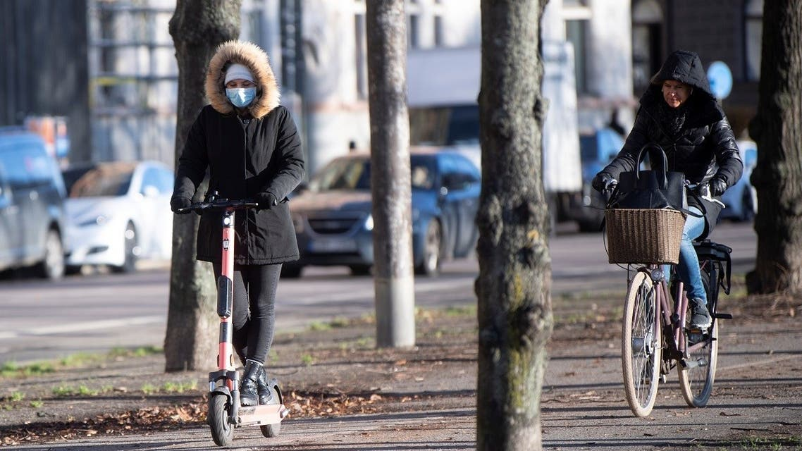 A woman rides an electric scooter wearing a protective mask, amid the continuous spread of the coronavirus disease (COVID-19) pandemic, along Standvagen in Stockholm. (Reuters)