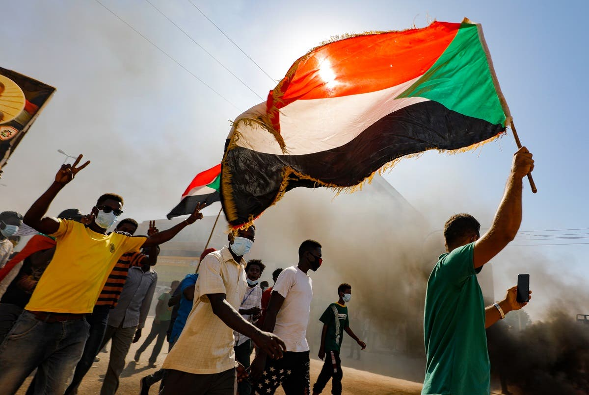 Sudanese youths wave the national flag as they rally in the streets of the capital Khartoum, chanting slogans and burning tires, to mark the second anniversary of the start of a revolt that toppled the previous government, on December 19, 2020. (AFP)
