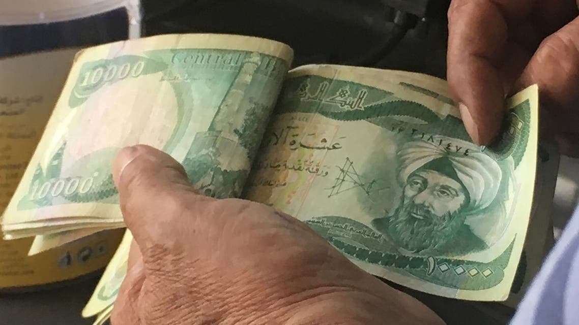 An Iraqi policeman pays for groceries with 10,000-Iraqi dinar banknotes on June 22, 2017, in the capital Baghdad. (AFP)