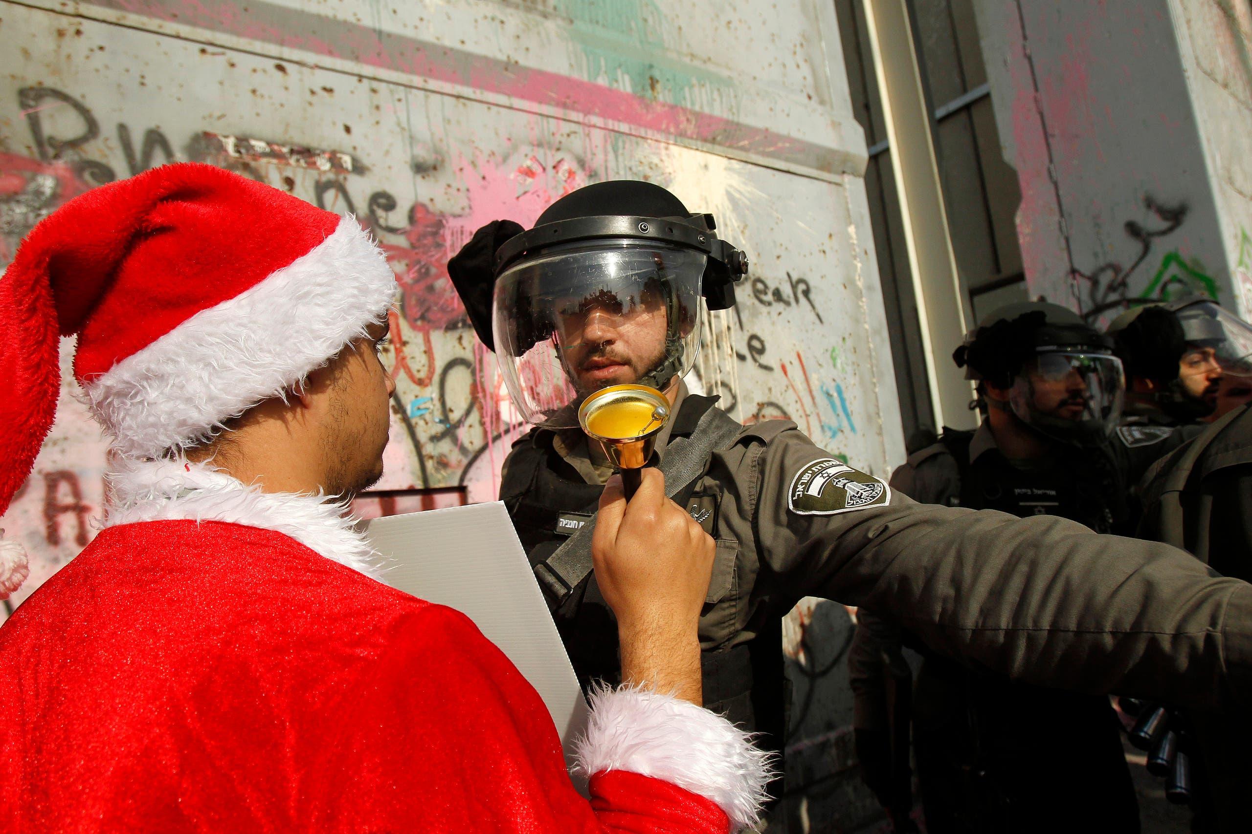 فلسطيني يرتدي ملابس سانتا كلوز مواجها جنديا إسرائيليا (أرشيفية- فرانس برس)
