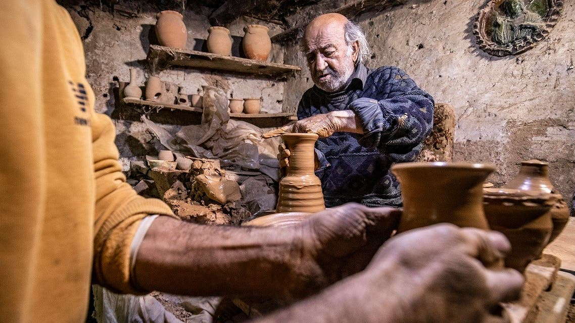 Syrian-Armenian potter Misak Antranik Petros uses an ancient pottery wheel to churn different types of pots at his workshop located inside an ancient mud-brick house near the city of Qamishli. (AFP)