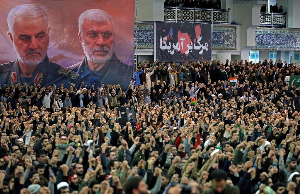 A handout picture provided by the office of Iran's Supreme Leader Ayatollah Ali Khamenei on January 17, 2020 shows Iranians chanting slogans during friday prayers in the capital Tehran, under portraits of slain Iranian commander Qasem Soleimani (L) and Iraq's Hashed al-Shaabi military network deputy chief Abu Mahdi al-Muhandis. (AFP)
