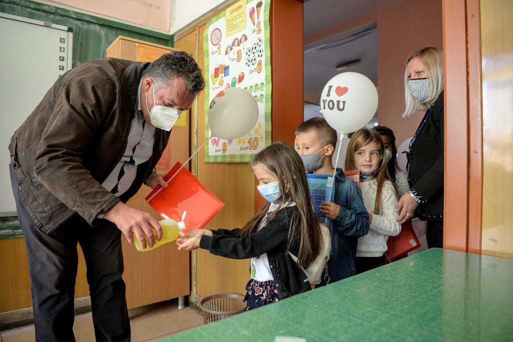 Macedonian school children wearing protective masks to prevent the spread of the novel coronavirus (covid-19) have their hands desinfescted on the first day of the new school year in Skopje on October 1, 2020. (AFP)