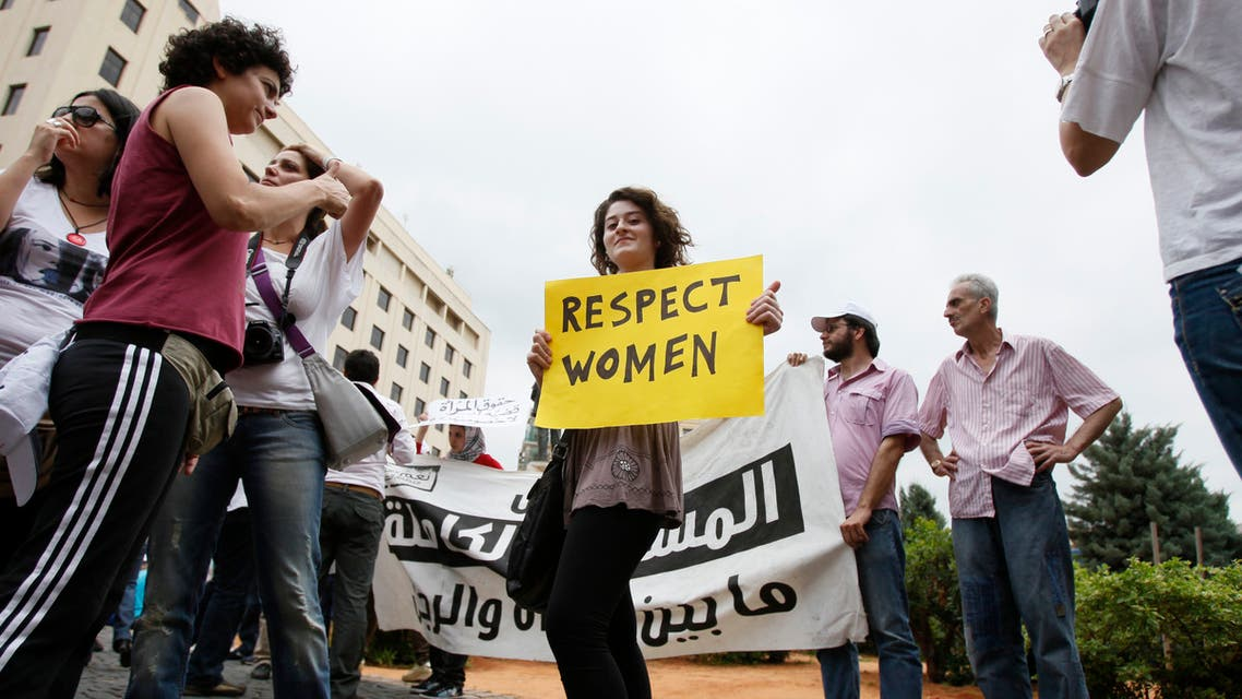 A female activist holding a placard stands amongst men during a protest against family violence near the parliament and government palace in Beirut May 29, 2011. (File photo: Reuters)