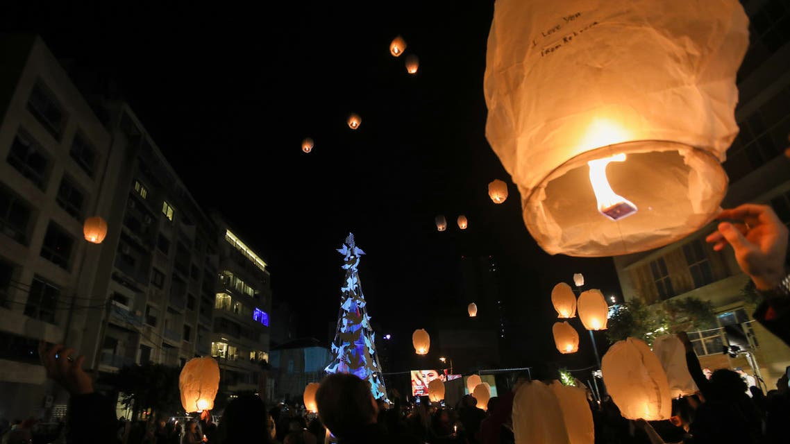 Lebanese launch lanterns in Beirut's Gemmayzeh neighborhood on December 20, 2020, during the lighting of a Christmas tree in memory of the victims of the August port blast. (AFP)