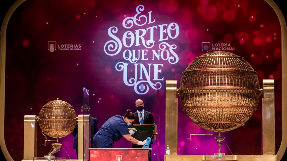 A worker disinfects an area at Madrid's Teatro Real opera house during Spain's bumper Christmas lottery draw known as El Gordo, or The Fat One, in Madrid, Spain, Tuesday, Dec. 22, 2020. (AP)