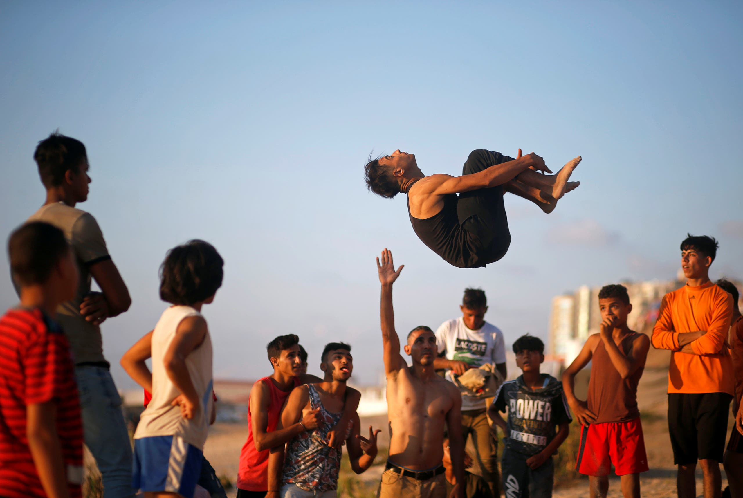 A Palestinian youth demonstrates his parkour skills on a beach as the coronavirus disease (COVID-19) restrictions ease in Gaza City. (Reuters)