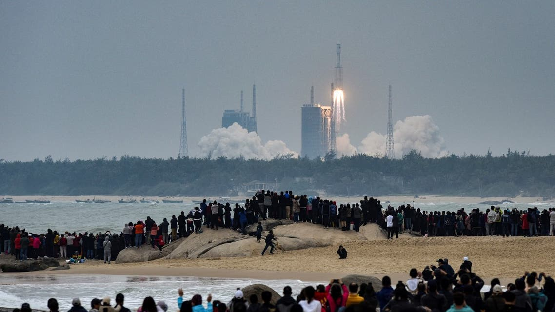 People watch a Long March-8 rocket, the latest China's Long March launch vehicle fleet, lifting off from the Wenchang Space Launch Center in southern China's Hainan province on December 22, 2020. (AFP)